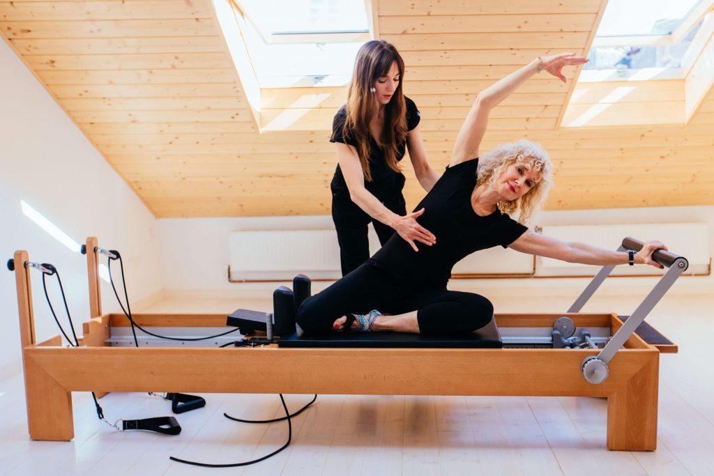 Elder women doing Pilates on reformer with trainer