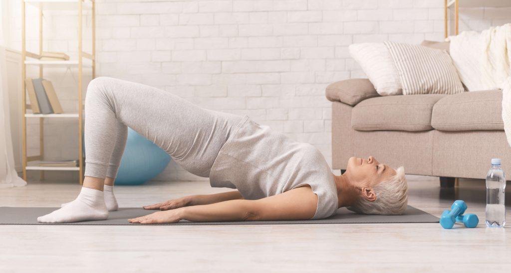 Elder women stretching hips on Pilates mat